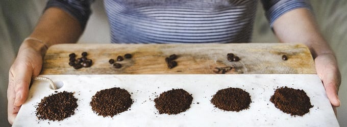 Different sized coffee grinds on a board for comparison
