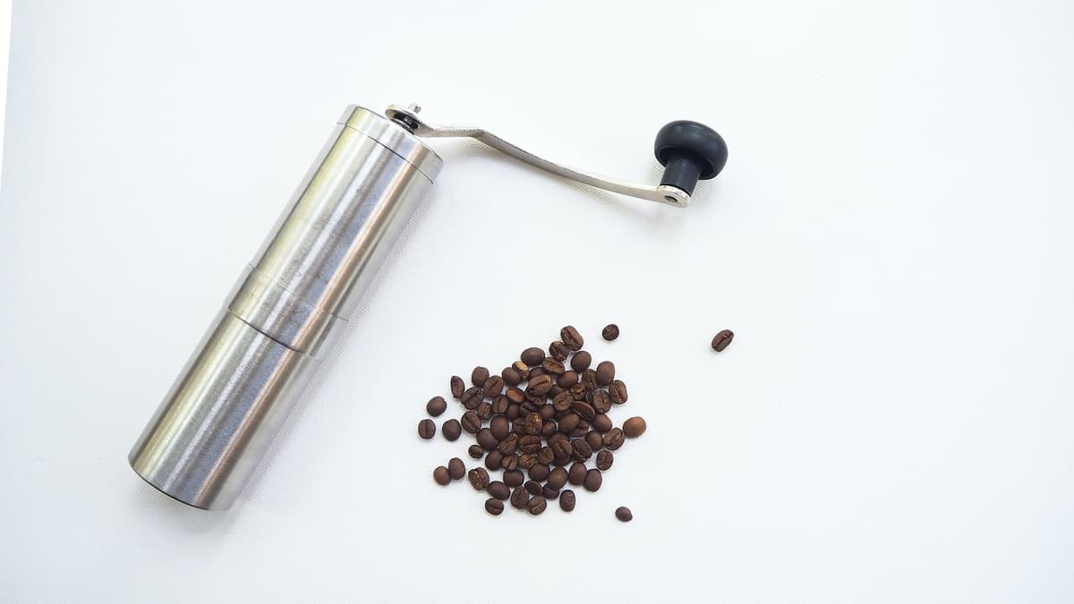 hand coffee grinder with coffee beans placed on white table