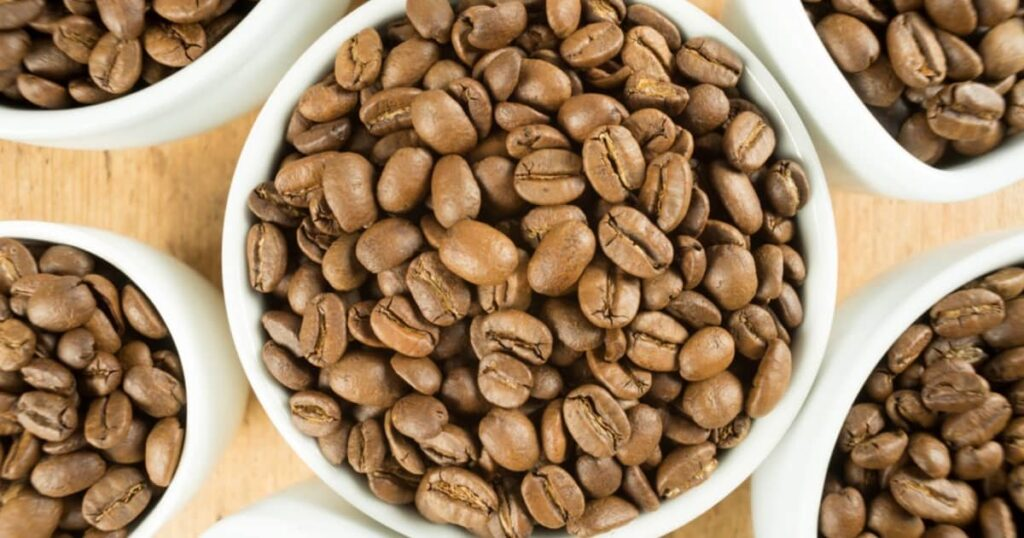 Light roast brown coffee beans in white cups on a wooden table top